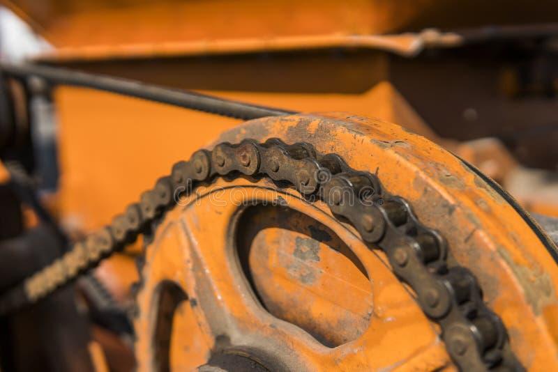 Il meccanismo della trasmissione a catena su un tracktor arancio fotografie stock libere da diritti