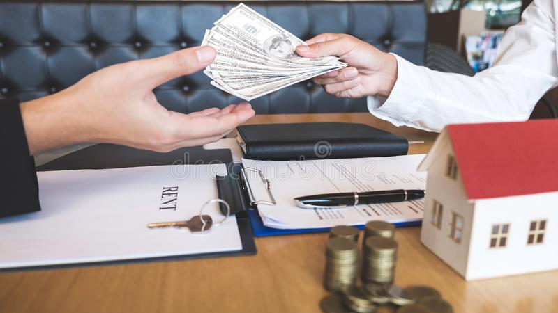 Il mediatore dell'agente immobiliare riscuote i fondi dal cliente dopo la firma del bene immobile del contratto di accordo con la fotografia stock libera da diritti