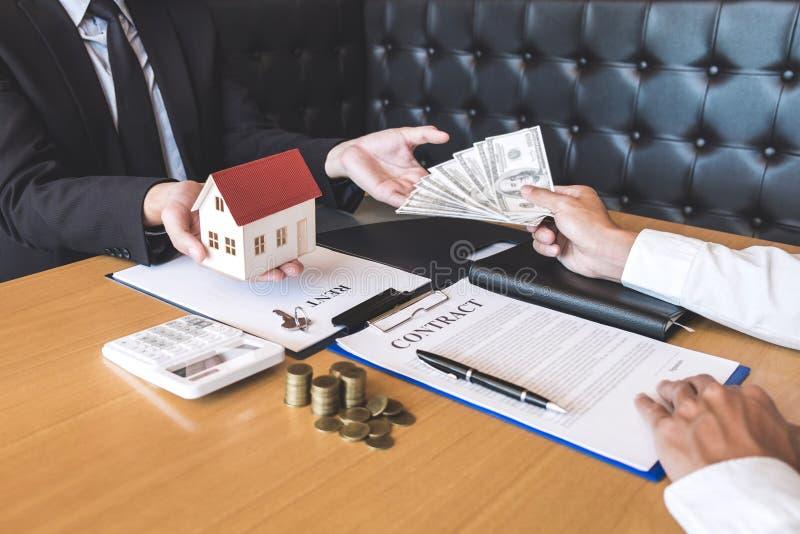 Il mediatore dell'agente immobiliare riscuote i fondi dal cliente dopo la firma del bene immobile del contratto di accordo con la immagini stock