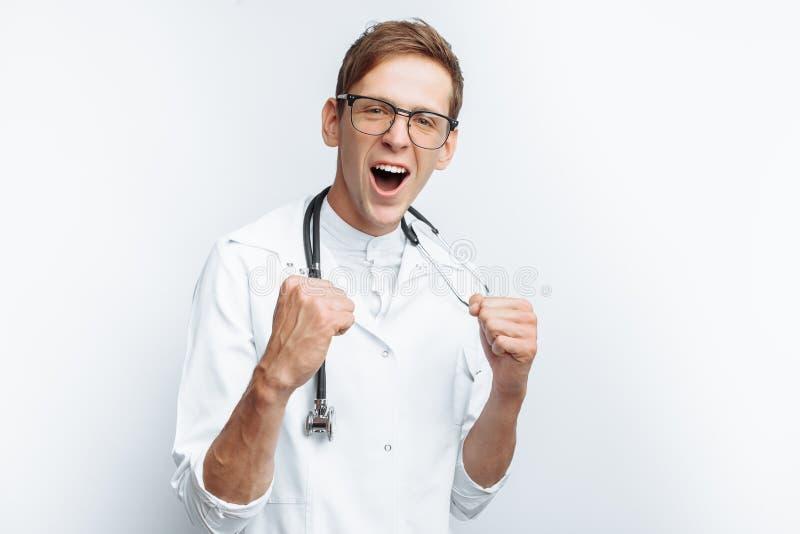 Il medico è soddisfatto con la riuscita operazione, il successo di giovane studente, su un fondo bianco fotografia stock libera da diritti