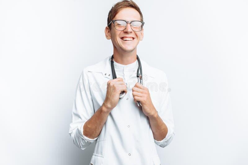Il medico è soddisfatto con la riuscita operazione, il successo di giovane studente, su un fondo bianco immagine stock
