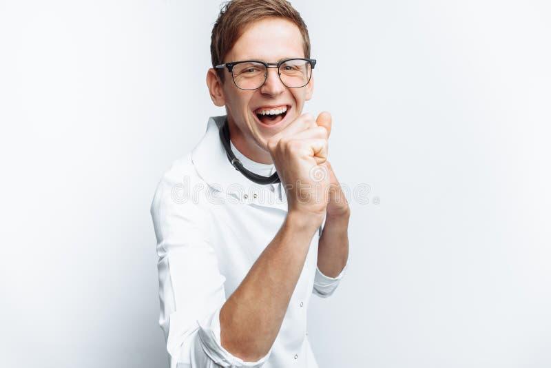 Il medico è soddisfatto con la riuscita operazione, il successo di giovane studente, su un fondo bianco immagini stock libere da diritti