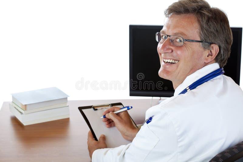 Il medico al suo scrittorio scrive la cartella sanitaria immagine stock libera da diritti