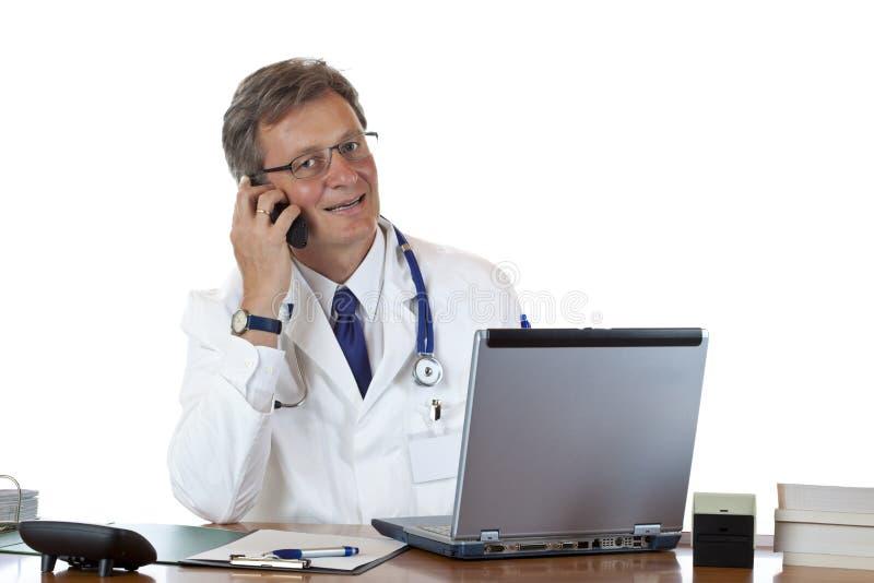 Il medico amichevole si siede allo scrittorio e fa una chiamata fotografie stock