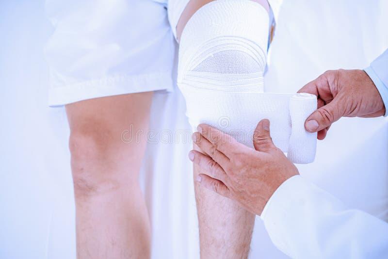 Il medico avvolge una bendatura elastica intorno all'articolazione del ginocchio fotografia stock libera da diritti