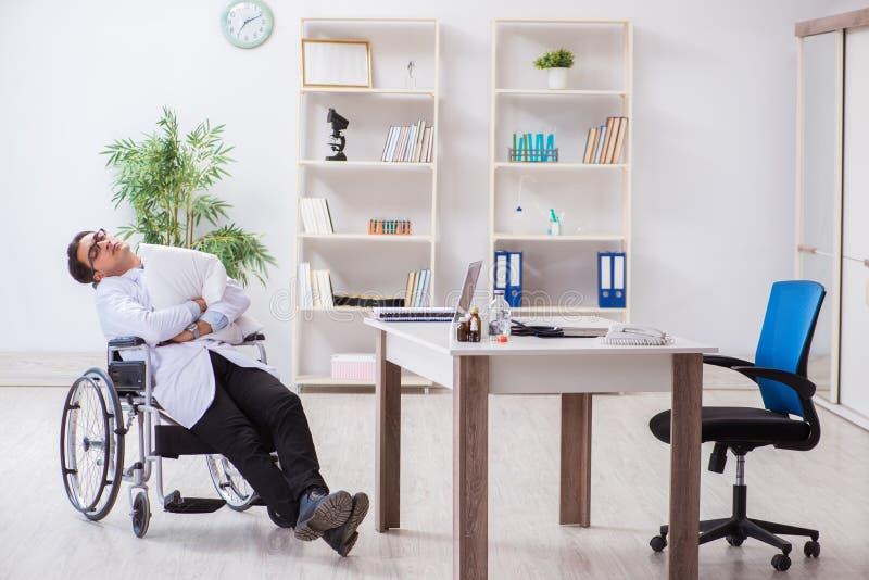 Il medico che riposa sulla sedia a rotelle in ospedale dopo il turno di notte immagine stock libera da diritti