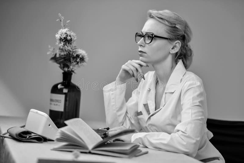 Il medico che si siede dietro lo scrittorio immagine stock