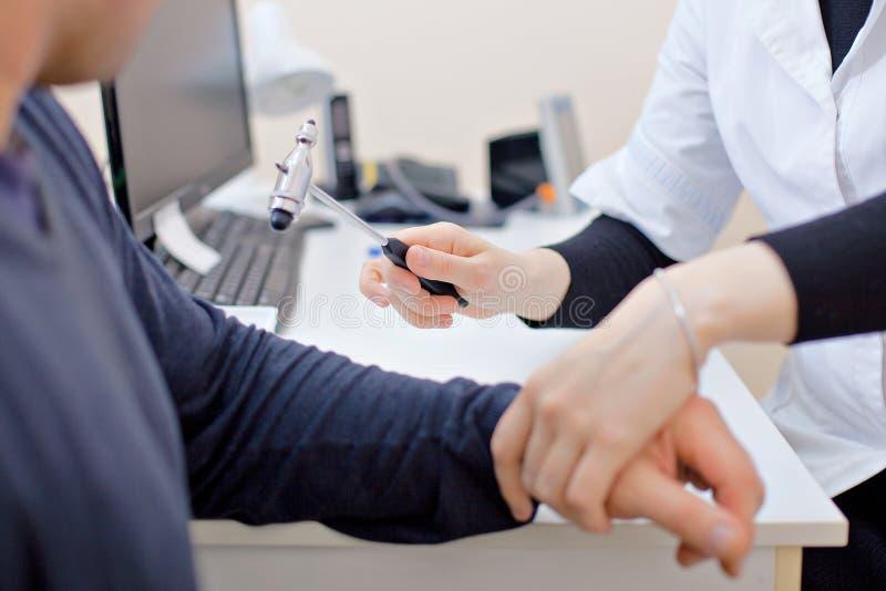 Il medico controlla i nervi sul gomito del paziente fotografia stock