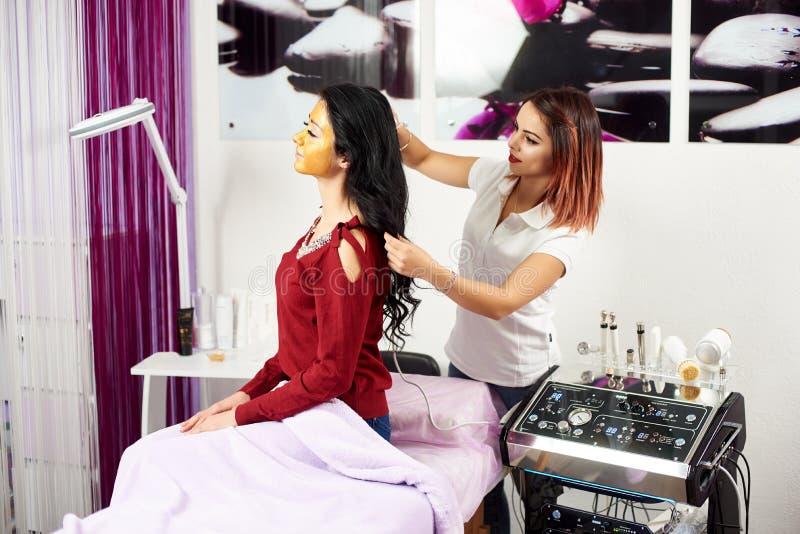 il Medico-cosmetologo rende alla procedura la terapia microcurrent su capelli della donna fotografia stock libera da diritti
