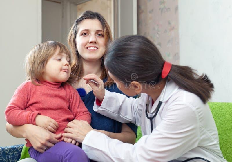 Il medico dei bambini che esamina 2 anni di bambino immagini stock