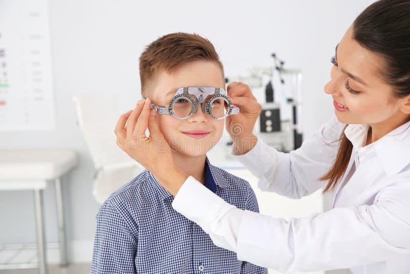 Il medico dei bambini che mette struttura di prova sul ragazzino nella clinica fotografia stock