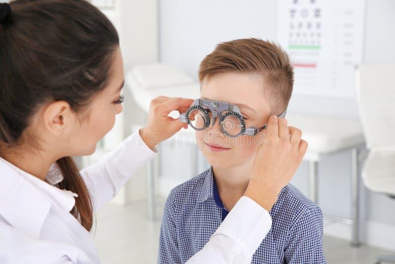 Il medico dei bambini che mette struttura di prova sul ragazzino nella clinica immagine stock libera da diritti