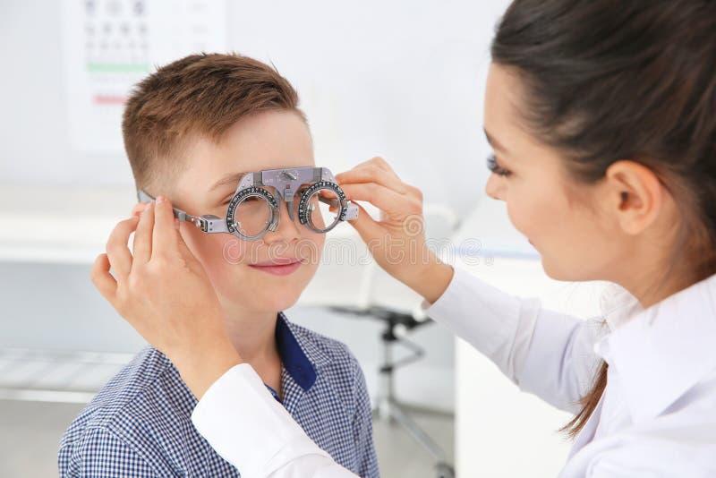Il medico dei bambini che mette struttura di prova sul ragazzino nella clinica fotografia stock libera da diritti