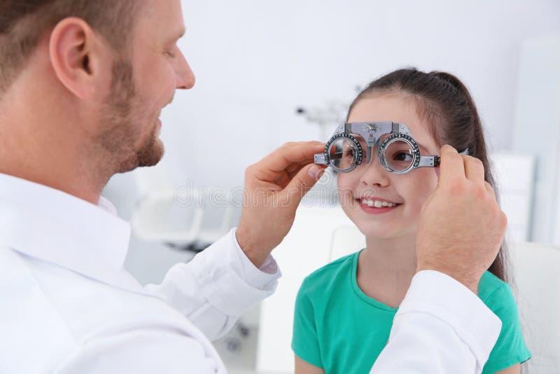 Il medico dei bambini che mette struttura di prova sulla bambina nella clinica immagini stock libere da diritti