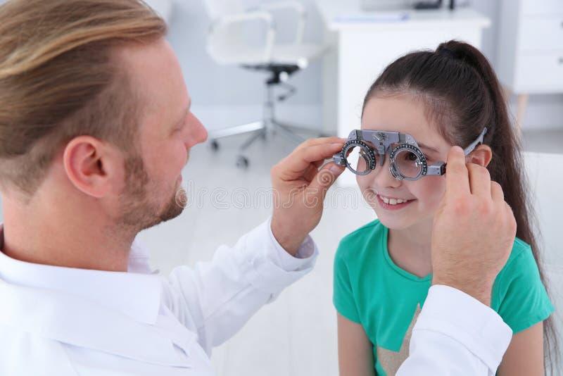Il medico dei bambini che mette struttura di prova sulla bambina nella clinica fotografia stock libera da diritti