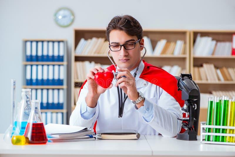 Il medico del supereroe che lavora nel laboratorio dell'ospedale fotografia stock