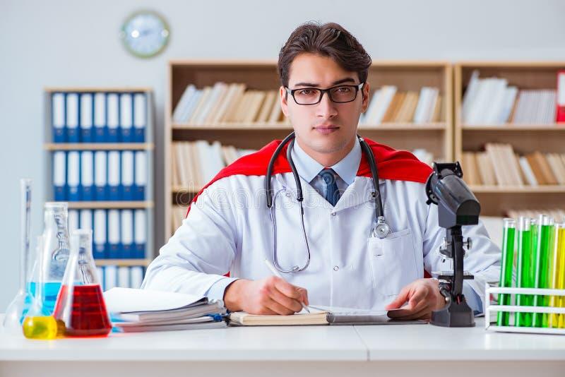 Il medico del supereroe che lavora nel laboratorio dell'ospedale immagine stock libera da diritti