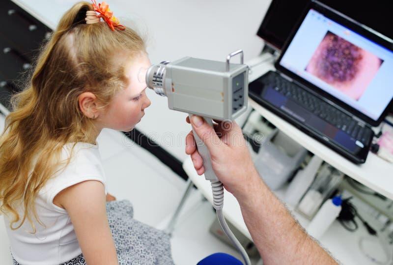 Il medico esamina il bambino speciale delle talpe dell'apparecchio medico fotografia stock