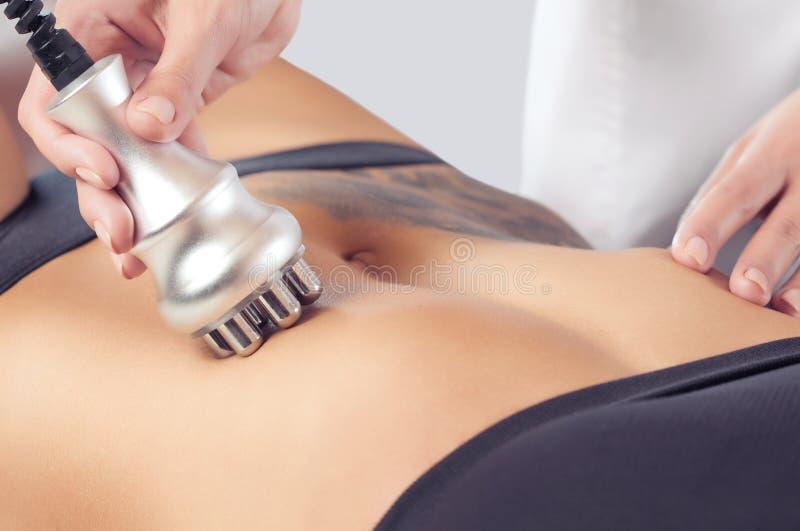 Il medico fa la procedura di sollevamento di rf sullo stomaco e sulle anche di una donna in un salone di bellezza fotografia stock