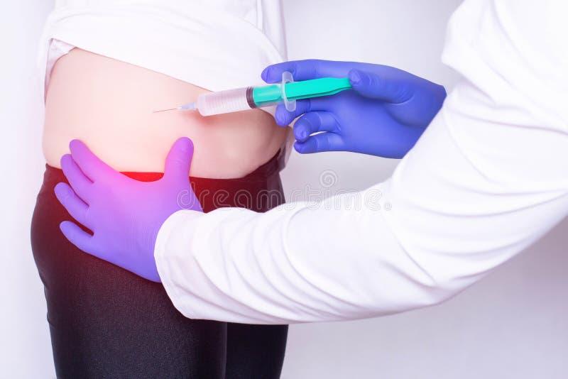 Il medico fa un'iniezione di acido ialuronico e del chondroprotector con l'anestesia nell'articolazione dell'anca della ragazza,  fotografia stock