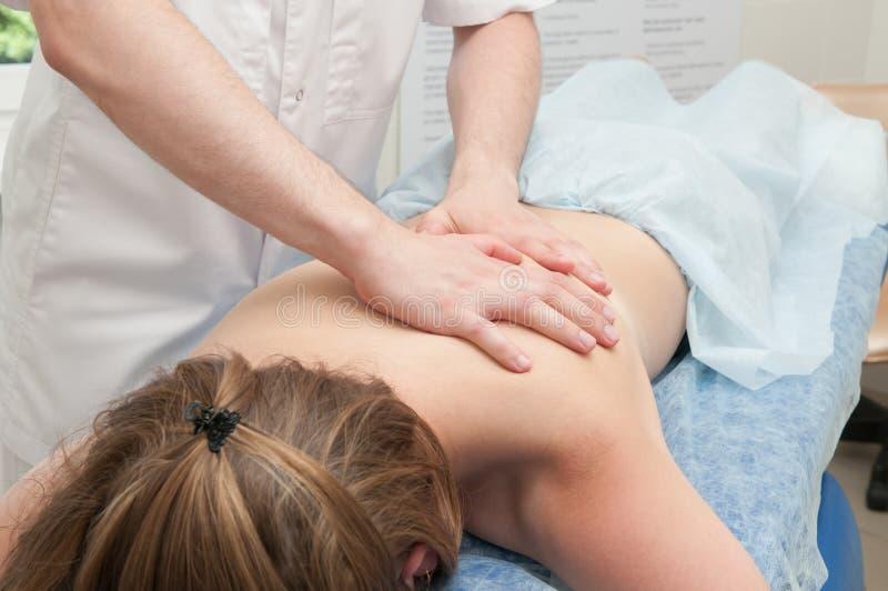 Il medico fa un massaggio del corpo ad una ragazza fotografie stock libere da diritti