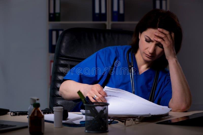 Il medico femminile invecchiato che lavora al turno di notte fotografia stock libera da diritti
