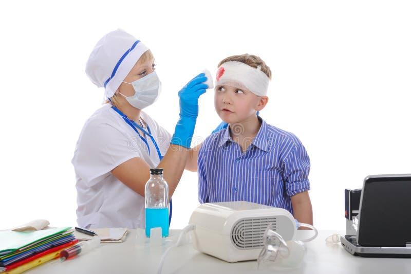 Il medico ha bendato la testa del ragazzo. fotografie stock