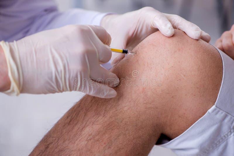 Il medico paziente maschio del visitng per l'inoculazione sparata immagini stock libere da diritti