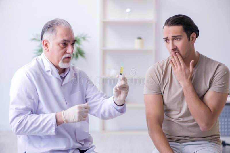 Il medico paziente maschio del visitng per l'inoculazione sparata fotografie stock libere da diritti