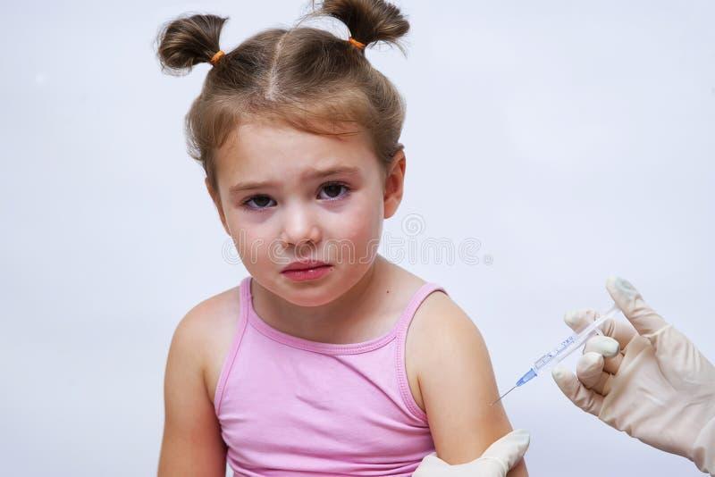 Il medico somministra un vaccino per iniezione a una bambina fotografia stock
