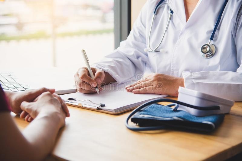 Il medico sta discutendo con il paziente dopo un exami fisico fotografie stock libere da diritti