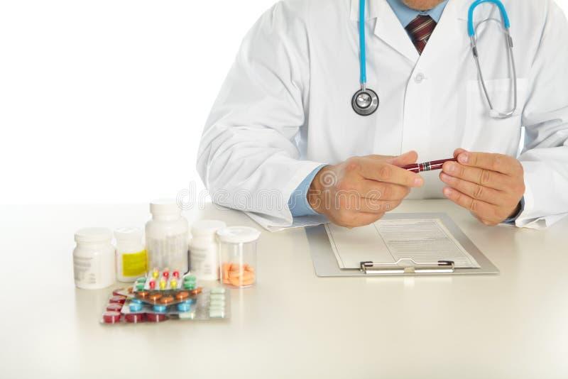 Il medico sta sedendosi alla tavola immagine stock