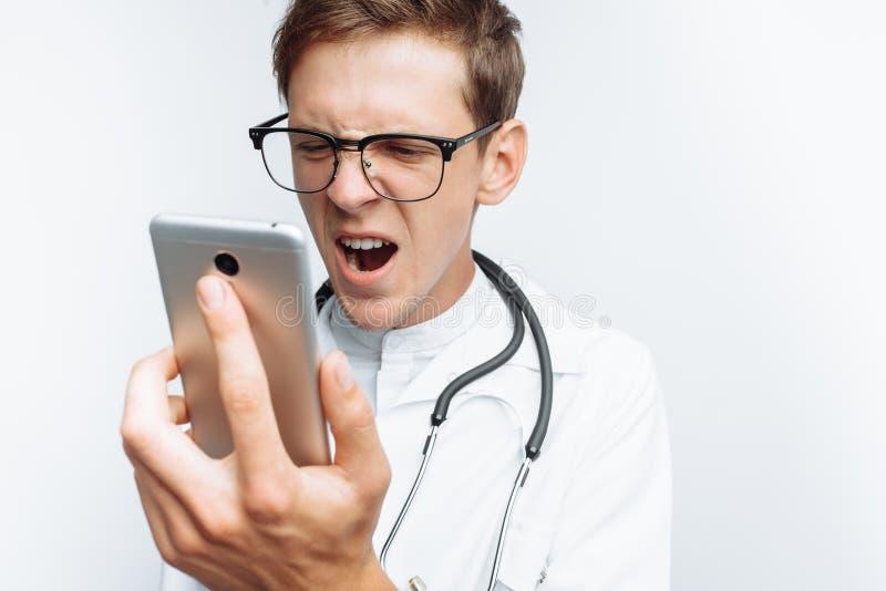 Il medico urla nel telefono, la conversazione con il paziente, le emozioni di giovane studente, fondo bianco fotografia stock libera da diritti