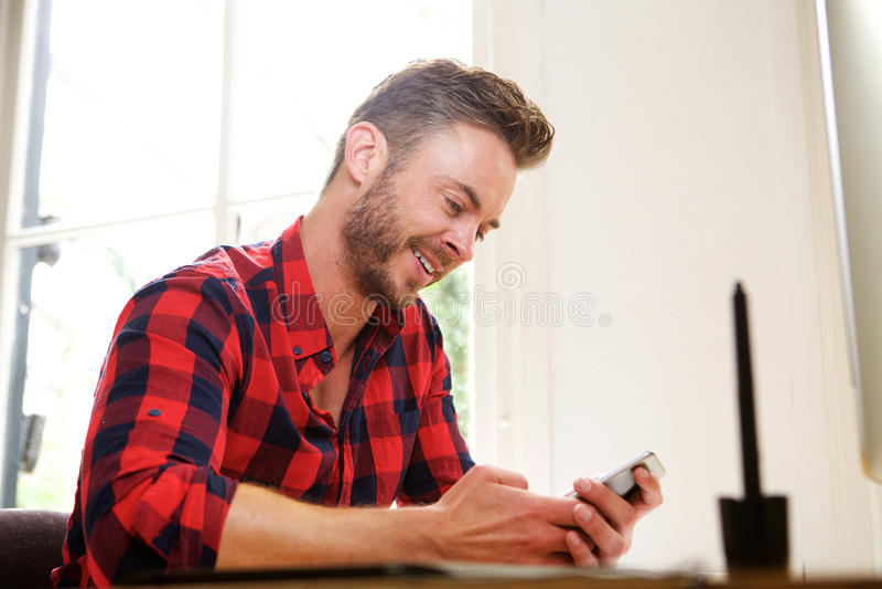 Il medio evo sorridente equipaggia la seduta allo scrittorio con il cellulare fotografia stock libera da diritti