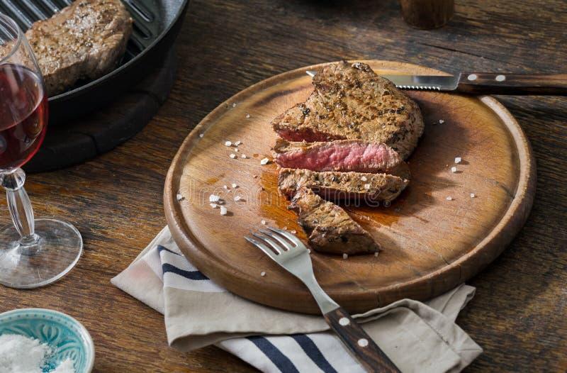 Il medium affettato ha grigliato la bistecca di manzo con vetro di vino rosso immagine stock libera da diritti