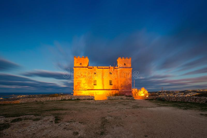 Il-Mellieha, Мальта - башня ` s St Agatha красная на сумраке с красивыми moving облаками стоковое фото