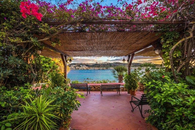 Il-Mellieha Malta - den härliga balkongen och bänkar surronded vid blommor med den Mellieha staden royaltyfri foto