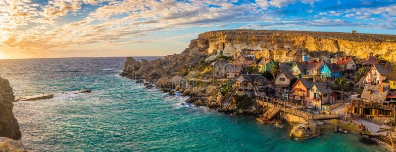 IL-Mellieha, Malta - opinión panorámica del horizonte del pueblo famoso de Popeye en la bahía del ancla en la puesta del sol imágenes de archivo libres de regalías
