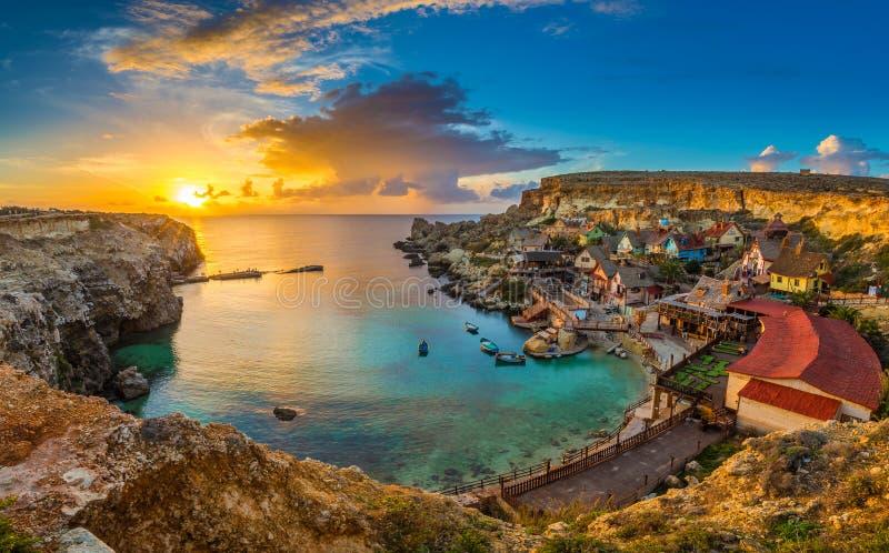 Il-Mellieha Malta - panorama- horisontsikt av den berömda Popeye byn på ankarfjärden på solnedgången arkivfoton