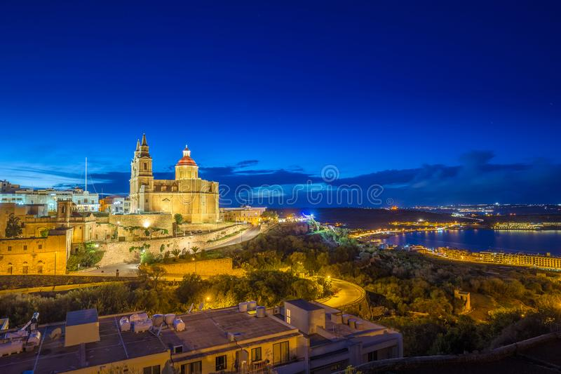 Il-Mellieha, Malta - Panoramic skyline view of Mellieha with the beautiful Mellieha Parish Church. And Mellieha bay at blue hour with the island of Gozo at stock images