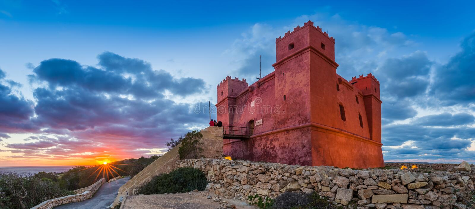 Il-Mellieha, Malta - Tourists watching sunset at St Agatha`s Red Tower with beautiful sky. And clouds stock image