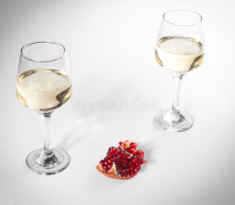 Il melograno tagliato si trova su un piatto bianco Due vetri di vino bianco fotografia stock libera da diritti