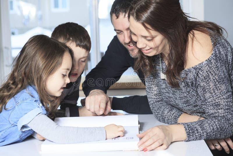 Il membro quattro della famiglia felice ha letto il libro di storia fotografie stock
