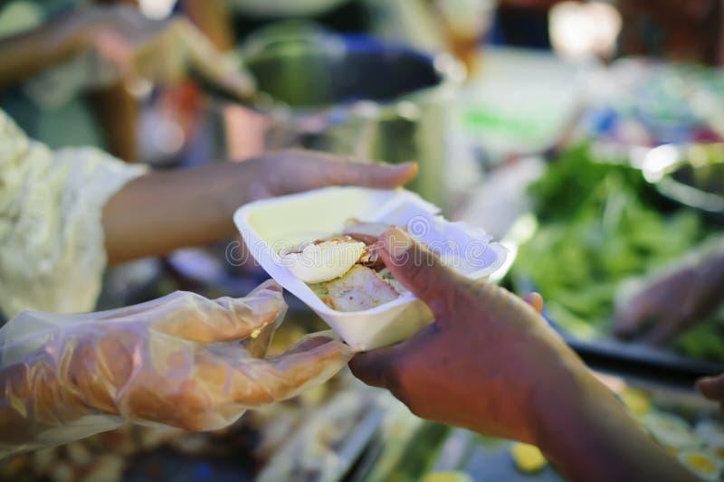 Il mendicante sta aspettando l'alimento dall'aiuto della carità: il concetto di supplica e di fame: I problemi di fame del povero immagine stock
