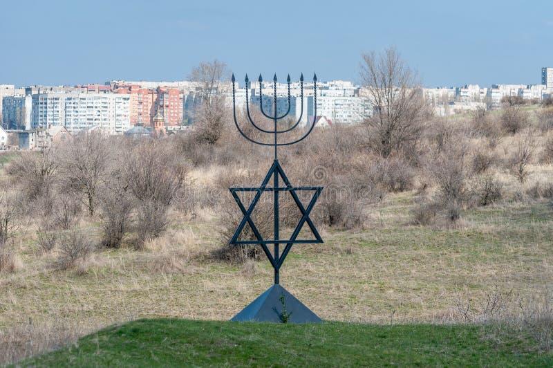 Il menorah è un simbolo di giudaismo Monumento alle vittime dell'olocausto nel villaggio di Bogdanovka l'ucraina immagine stock