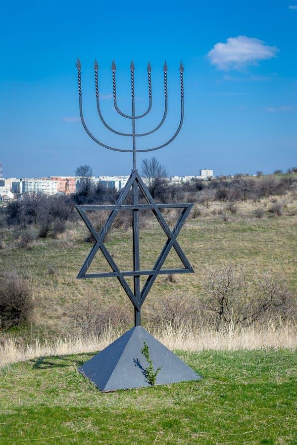 Il menorah è un simbolo di giudaismo Monumento alle vittime dell'olocausto nel villaggio di Bogdanovka l'ucraina immagine stock libera da diritti