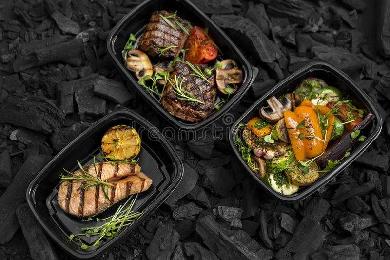 Il menu arrostito di recente cucinato per porta via in scatole nere fotografia stock libera da diritti