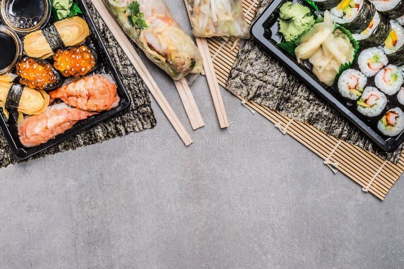 Il menu dei sushi con il nigiri, il maki e l'interno rotola, l'estate arriva a fiumi gli involucri di carta di riso su gray su fo fotografia stock