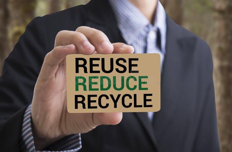 Il messaggio del biglietto da visita della tenuta dell'uomo d'affari ricicla, si riduce, riutilizza fotografia stock libera da diritti