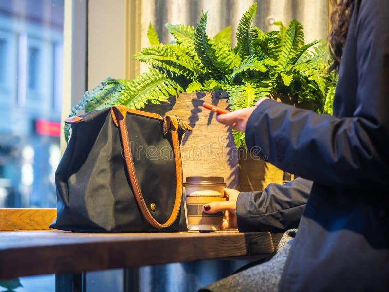 Il messaggio di testo di battitura a macchina della donna di affari sullo Smart Phone in un caffè, si chiude su del telefono femm fotografia stock